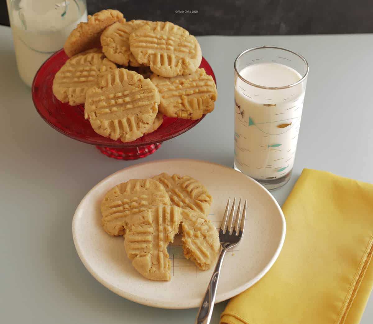 Peanut butter cookies on a dessert plate with a glass of milk next to it and a platter of peanut butter cookies behind it