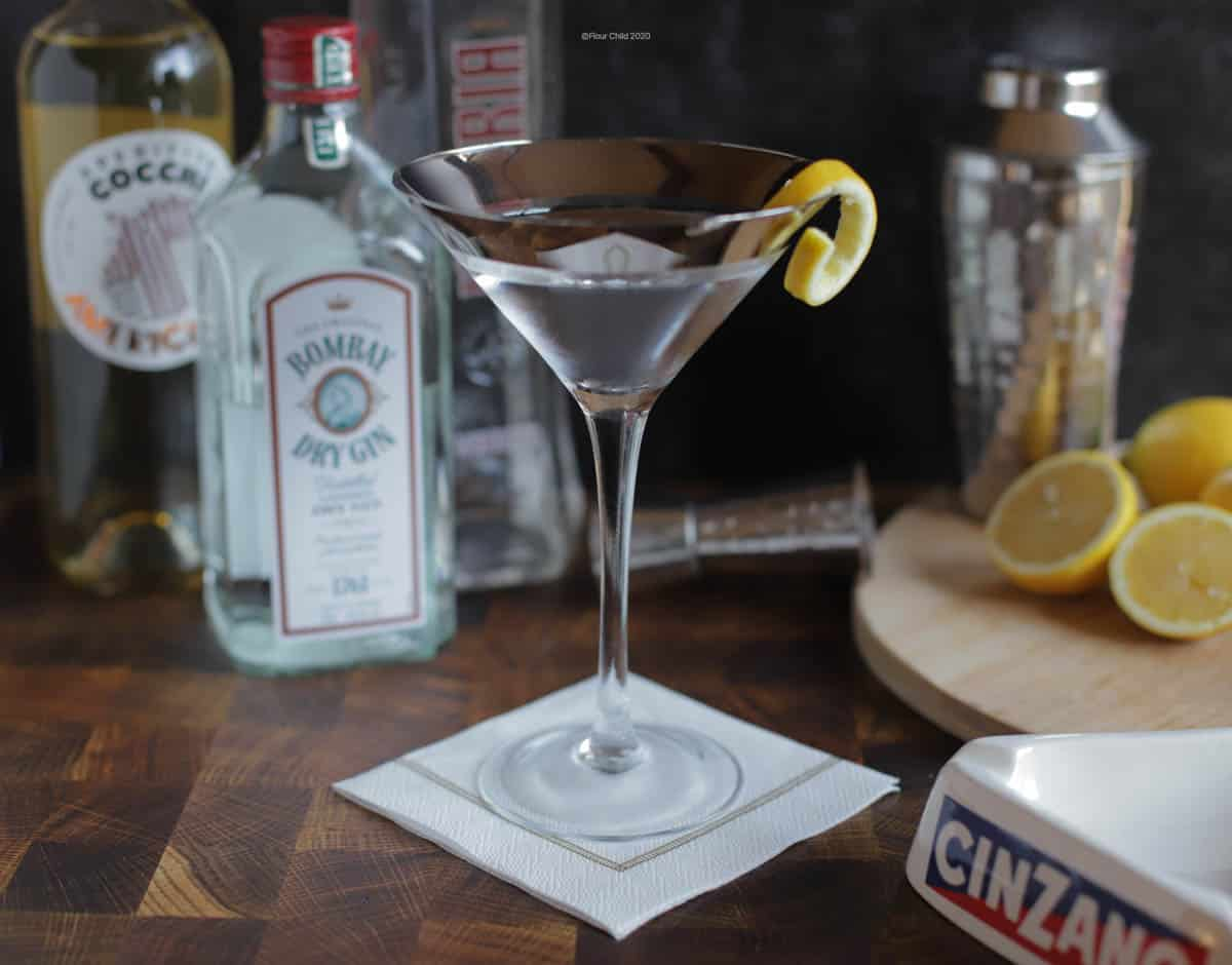 A Vesper Martini in a chilled cocktail glass with bottles and lemons in the background