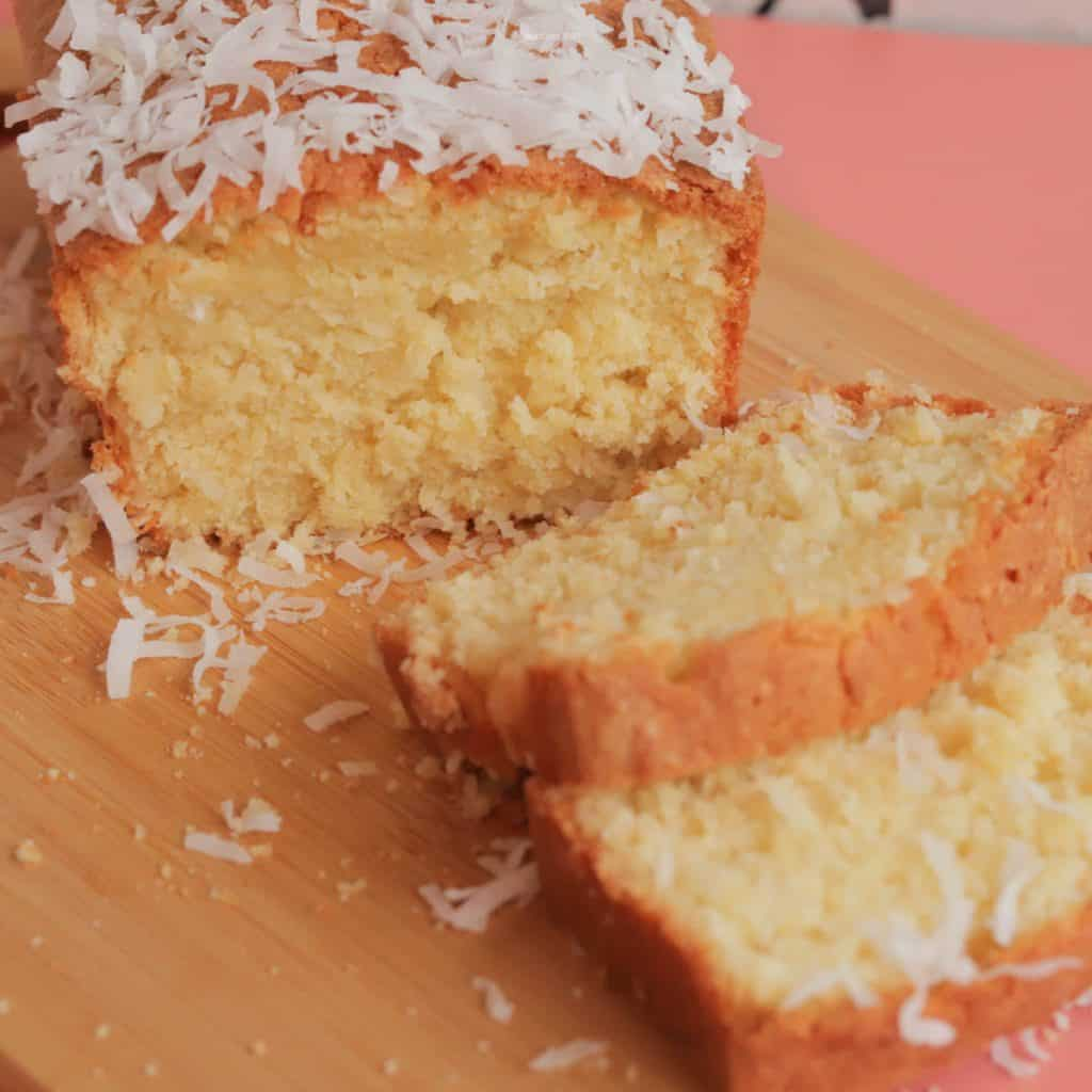 Two slices of coconut poundcake in front of the whole poundcake, with coconut sprinkled on top