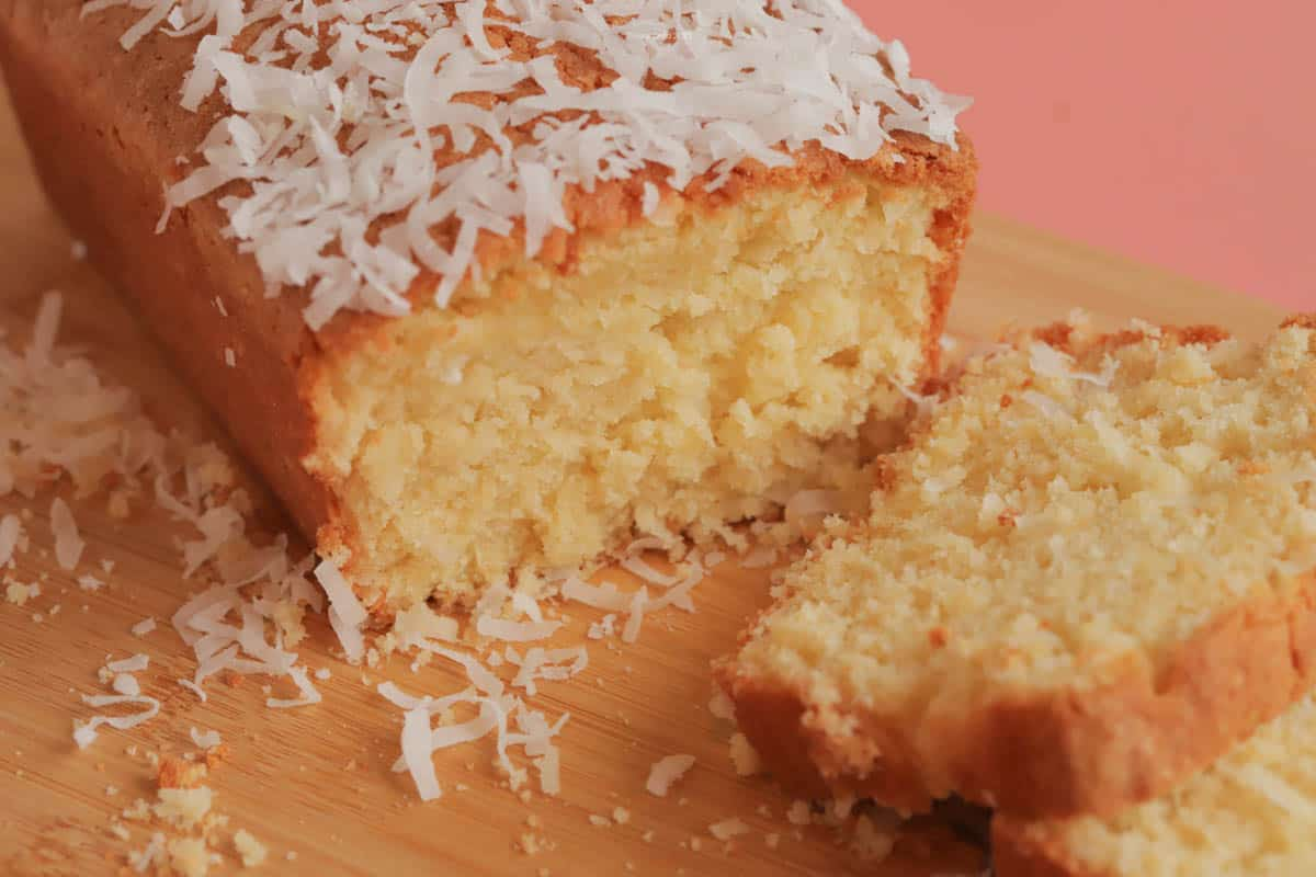 A slice of coconut poundcake in front of the whole poundcake, with coconut sprinkled over the top