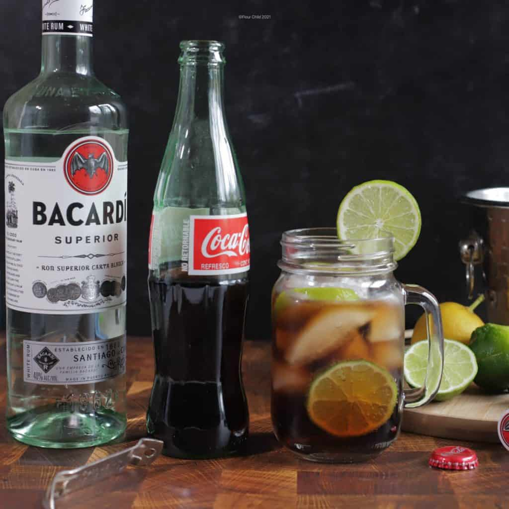 A scene of a Cuba Libre cocktail with a bottle of Coke and Bacardi rum