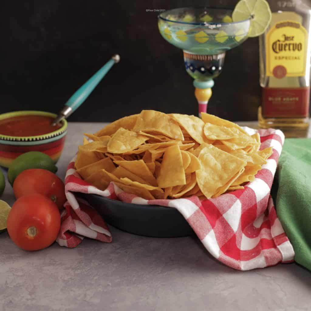 Basket of corn tortilla chips next to a bowl of salsa and a margarita