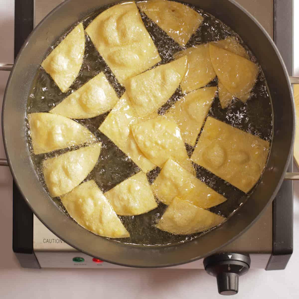 Corn tortillas frying in pan of hot oil