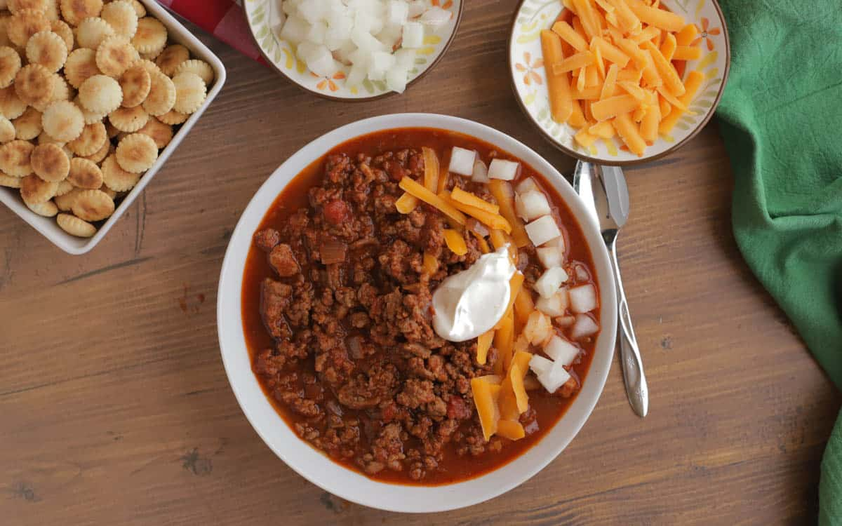 Bowl of chili topped with cheese, onions, and sour cream