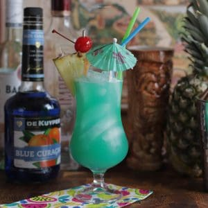 A Blue Hawaii cocktail in a hurricane glass with fruit and umbrella