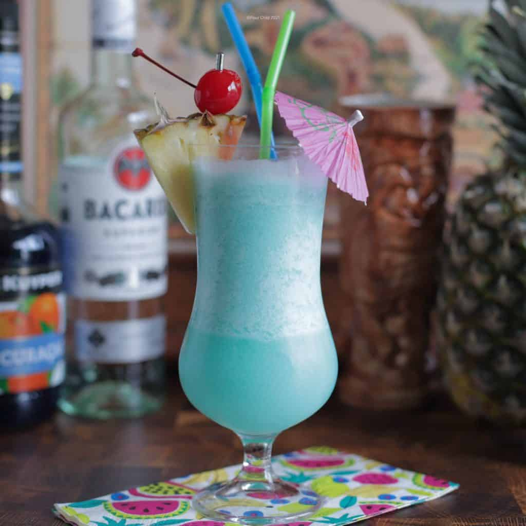 Blue Hawaiian cocktail with spirits and tiki mugs