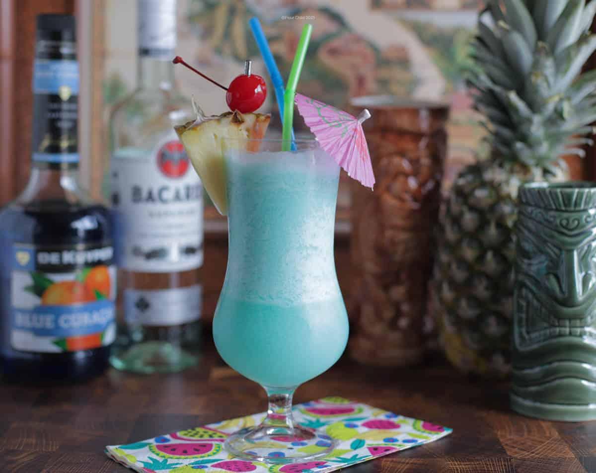 Blue Hawaiian cocktail with spirits and tiki mugs