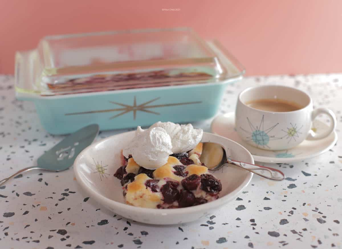 Cherry cobbler in a bowl with ice cream on top, coffee cup and casserole dish in background