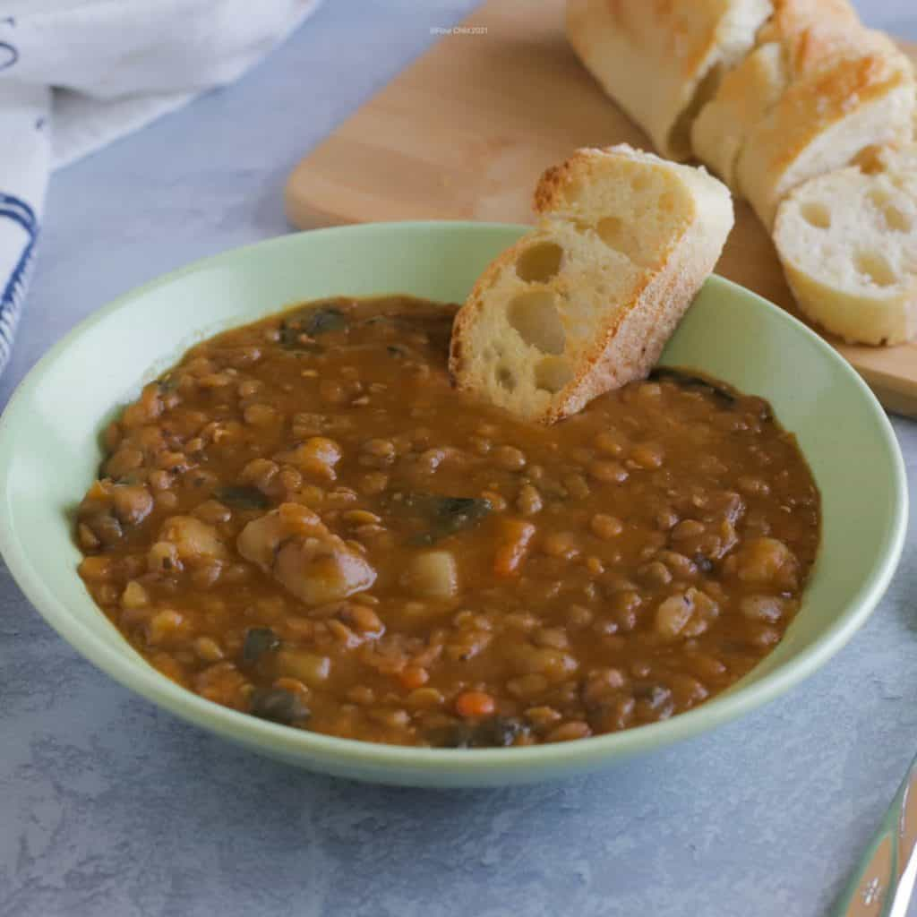 Bowl of simple lentil soup served with French bread on the side.