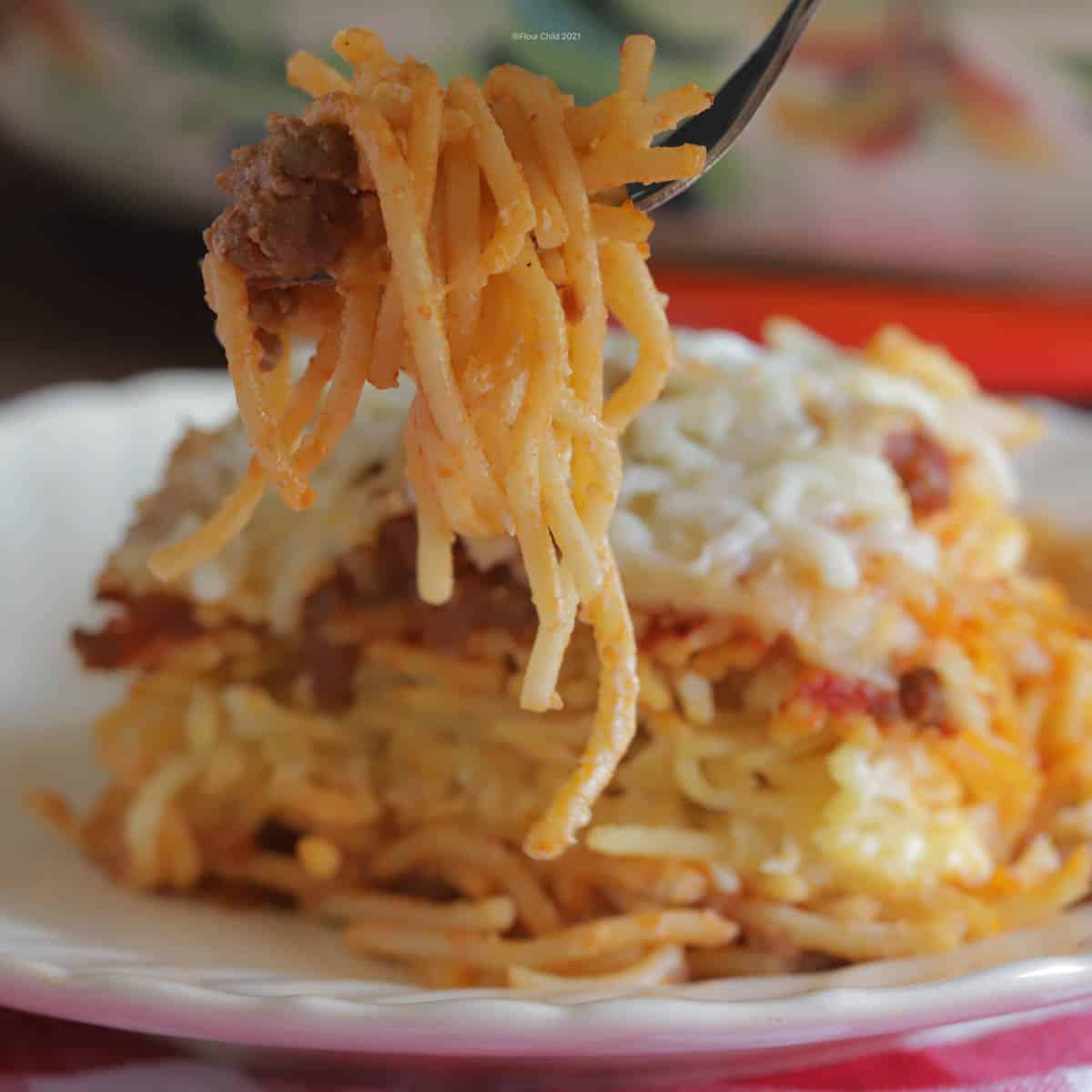 Fork scooping some spaghetti from a slice of baked spaghetti on a plate