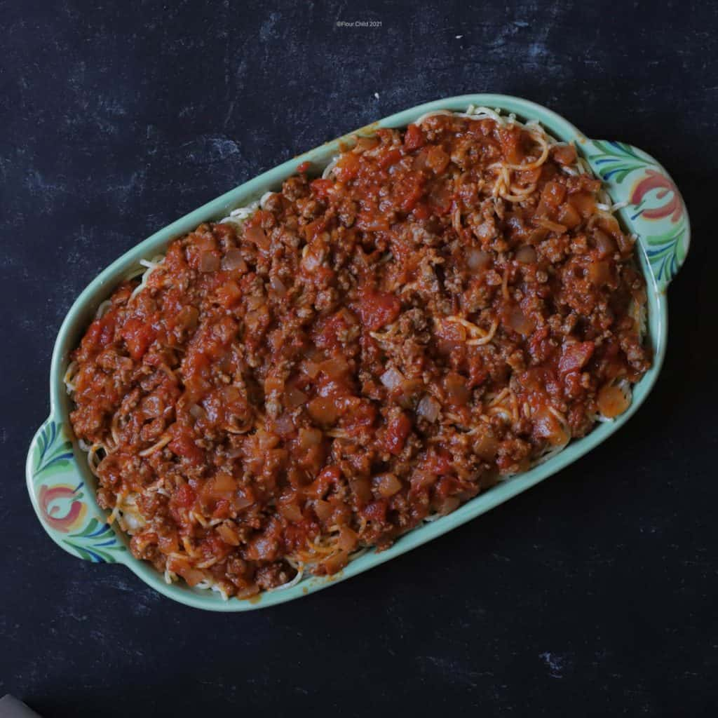 Add second half of spaghetti then second half of meat sauce