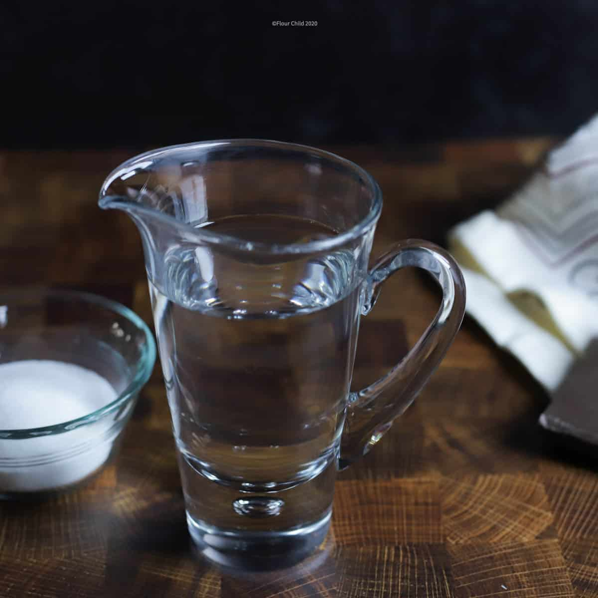 a small pitcher of simple syrup with a small bowl of sugar