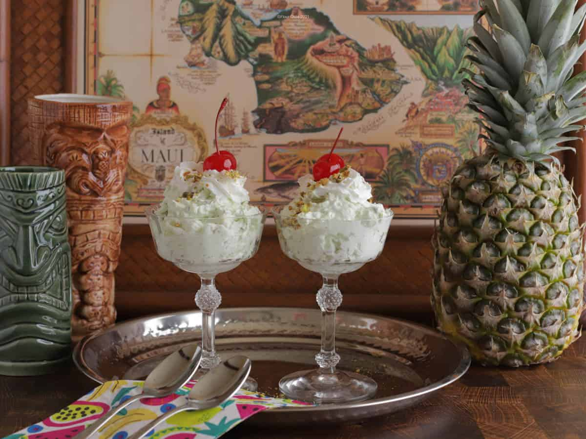 Two servings of Watergate salad in decorative glass cups on a silver tray