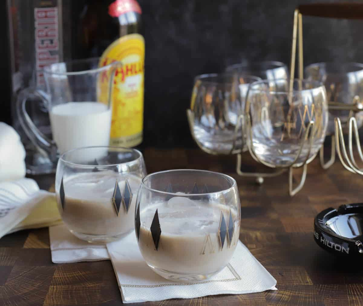 Two white russian cocktails with extra glasses