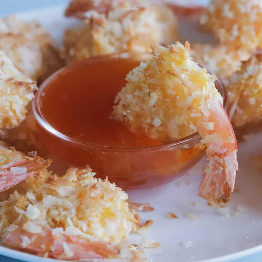 Coconut shrimp on a plate, with a small bowl of apricot dipping sauce that has a shrimp dipped into it.