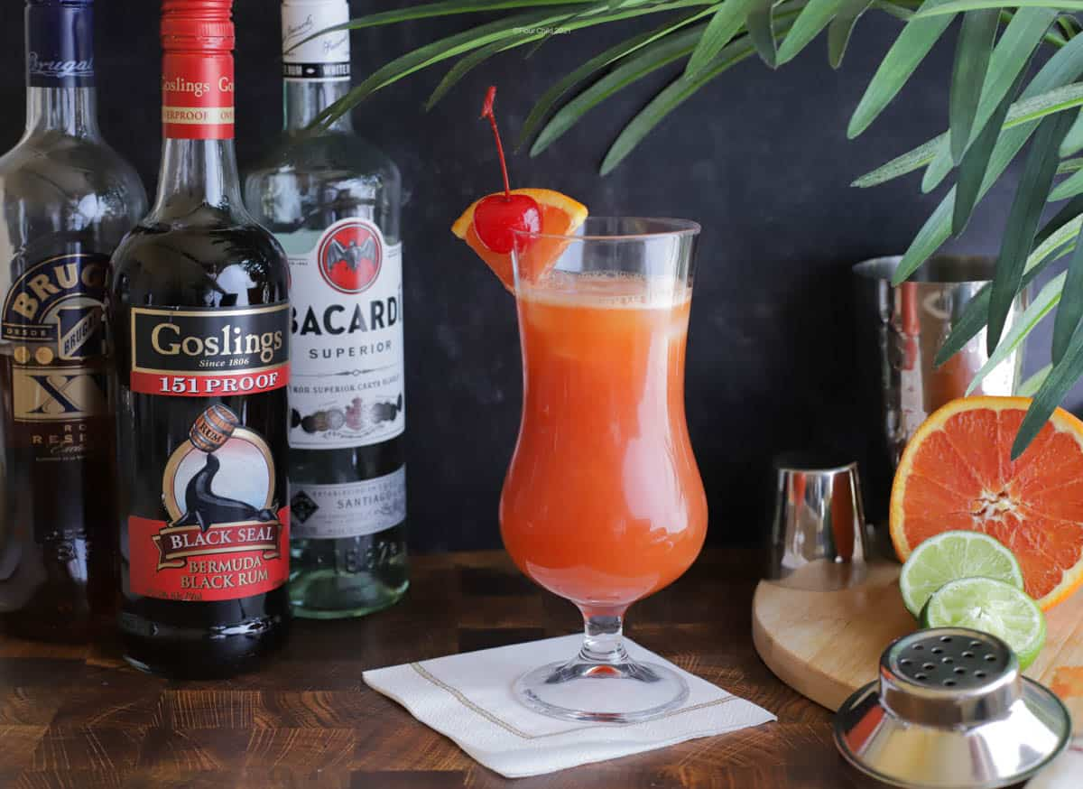 A tangy rum-based cocktail featured in a hurricane glass surrounded by three types of rum