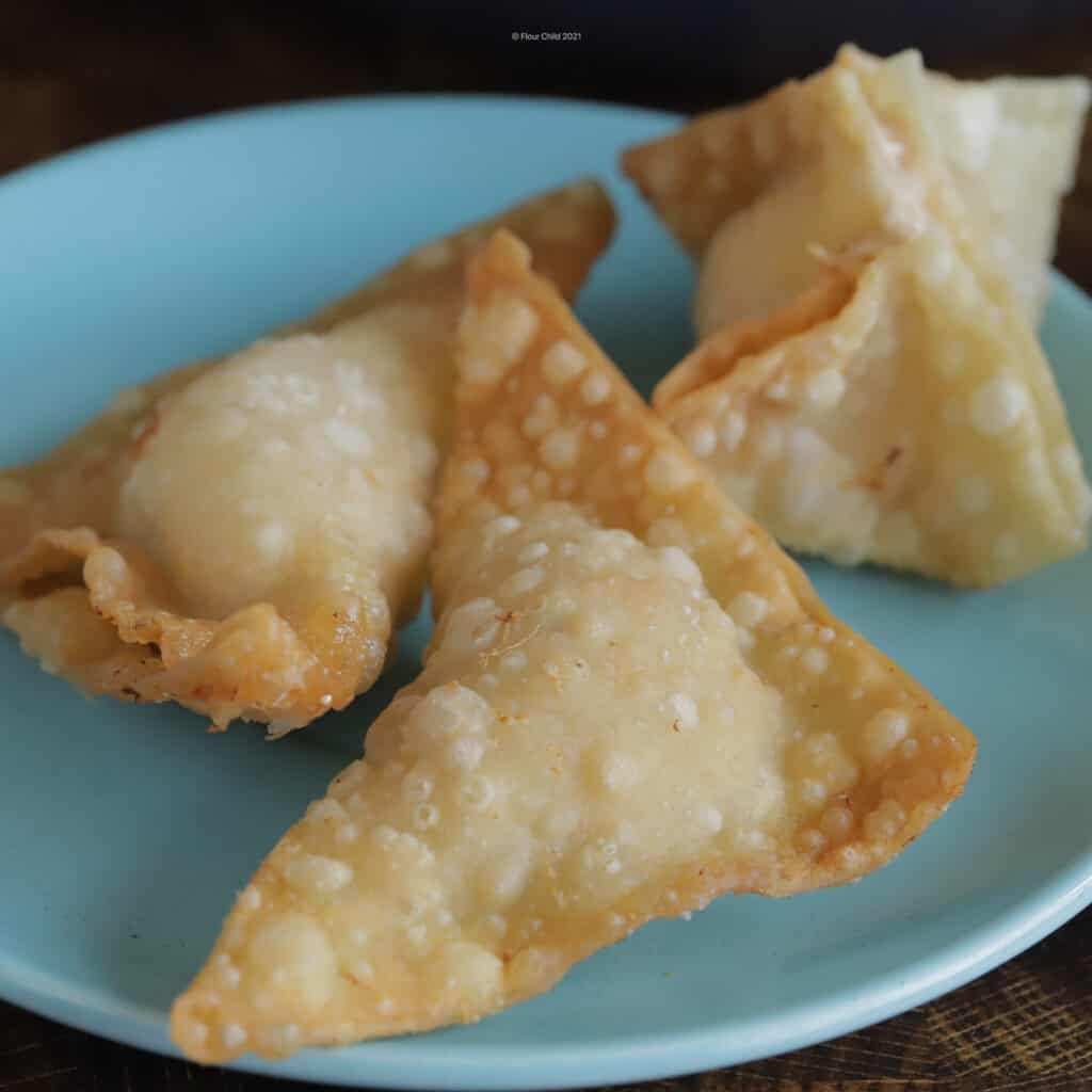 Three pieces of crab rangoon on a blue plate.