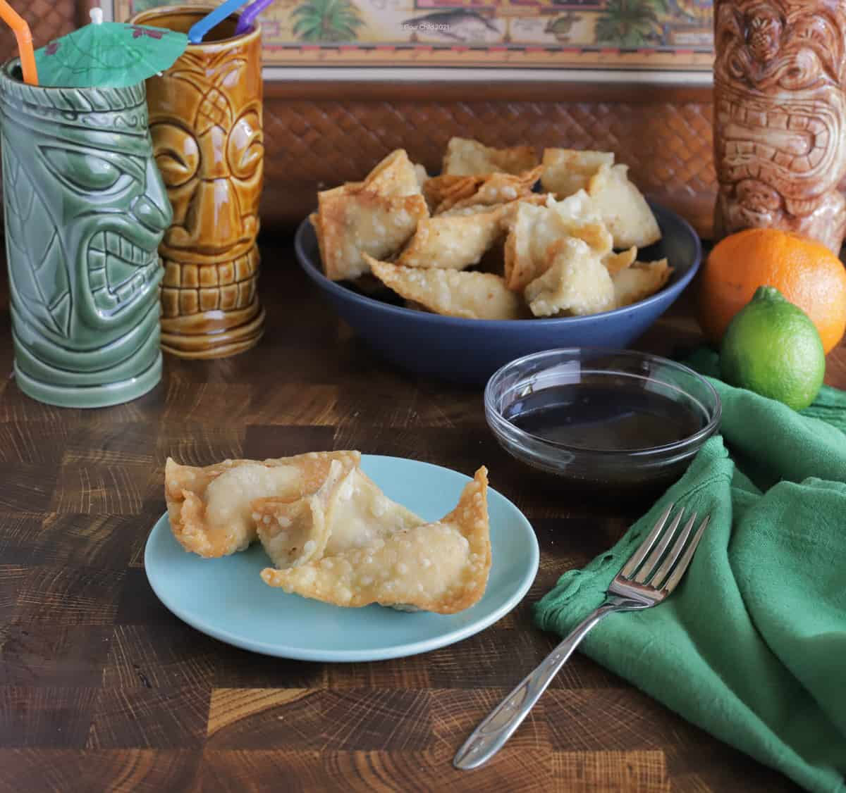 Two pieces of crab rangoon on a blue plate with a blue bowl of crab rangoon in the background