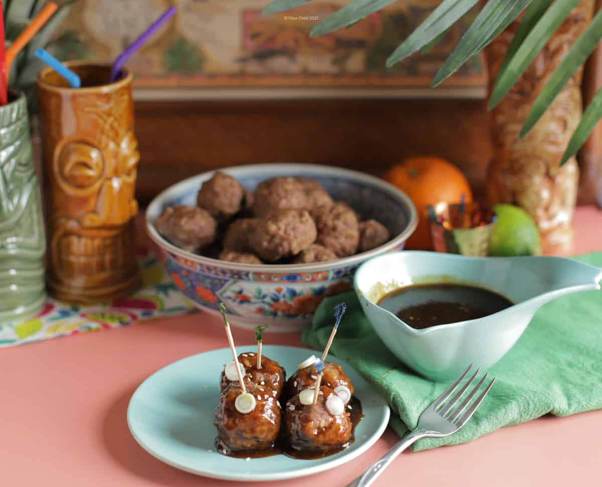 Four meatballs on a small plate with a side of teriyaki sauce, and a bowl of additional meatballs in the background