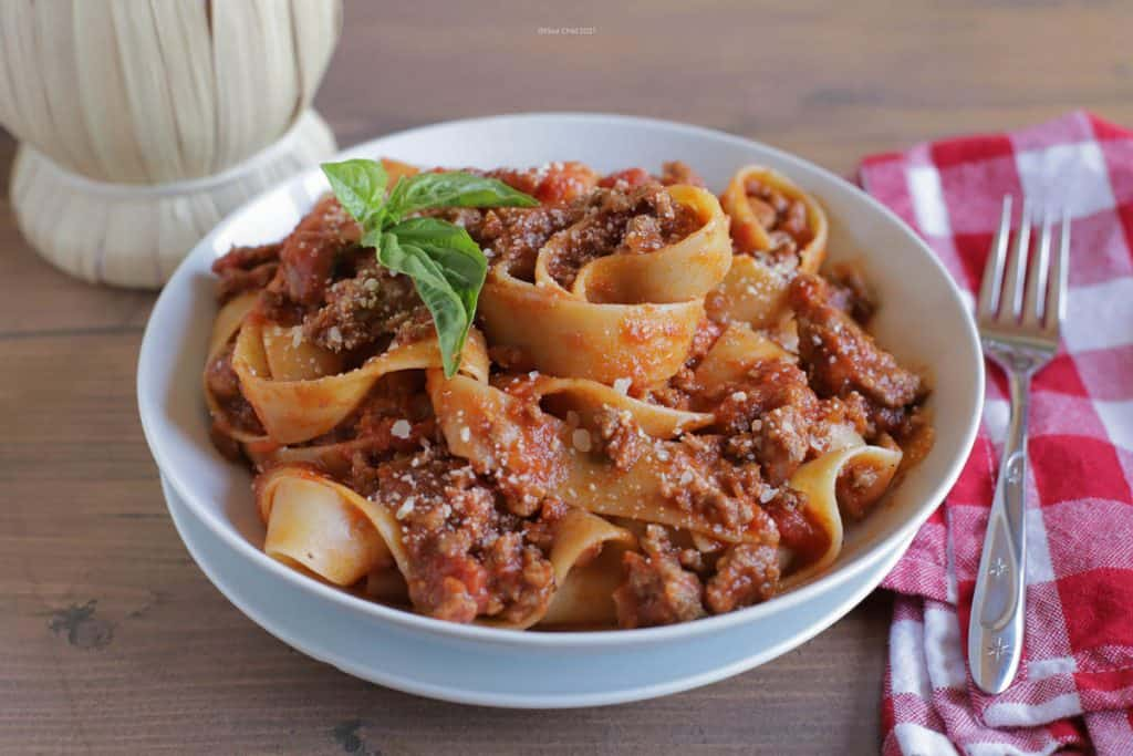 A white bowl filled with homemade bolognese sauce with pappardelle pasta and topped with a basil leaf