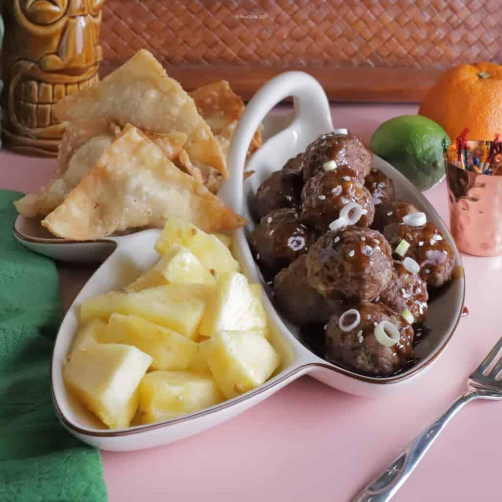 Divided 3-way pupu platter tray with crab rangoon, teriyaki meatballs, and fresh pineapple chunks.