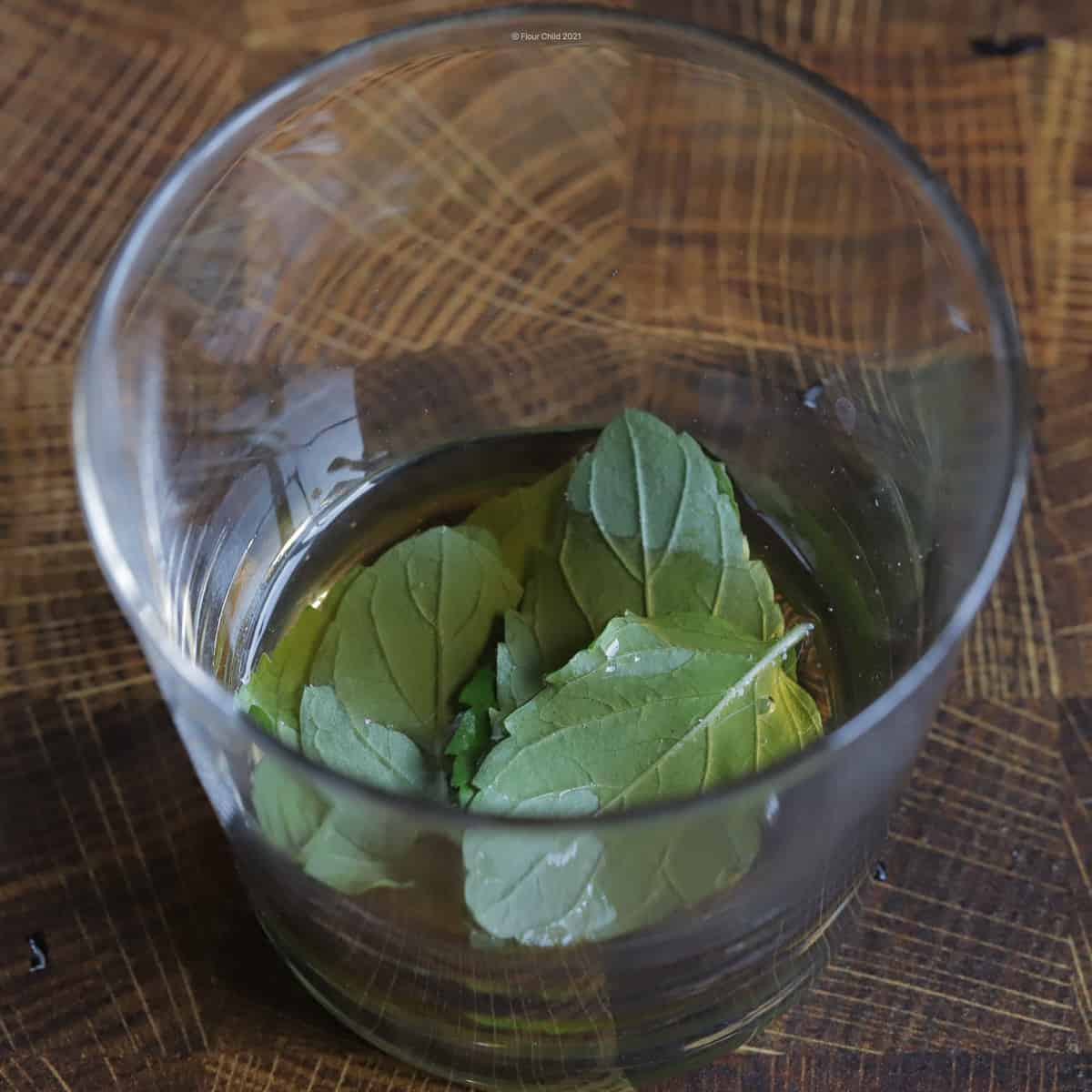 mint leaves muddled in simple syrup