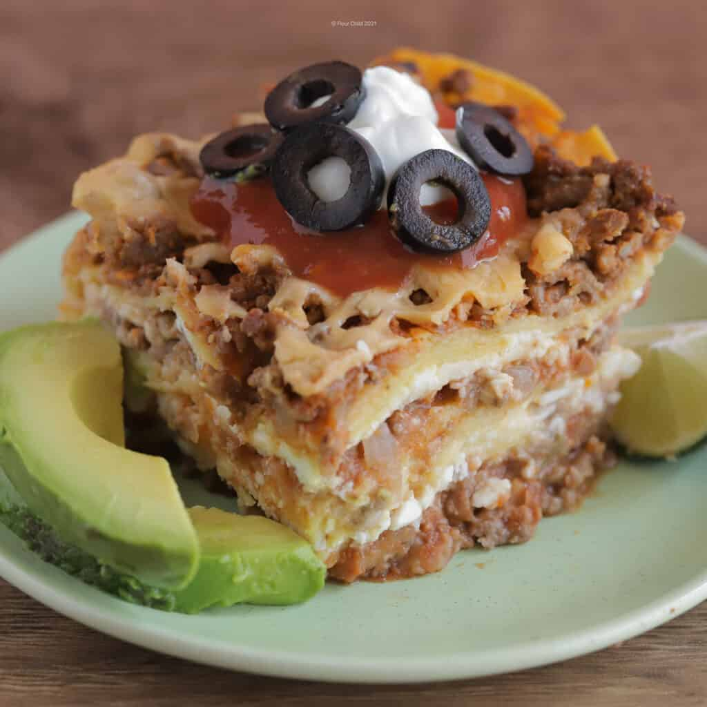 Slice of Mexican Lasagna on a green plate topped with sour cream and olives, with sliced avocados and lime on the side.