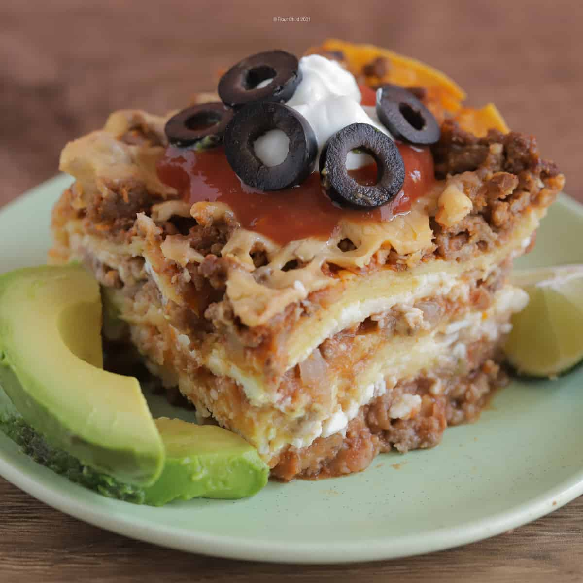 Slice of Mexican Lasagna on a green plate topped with sour cream and olives, with sliced avocados and lime on the side
