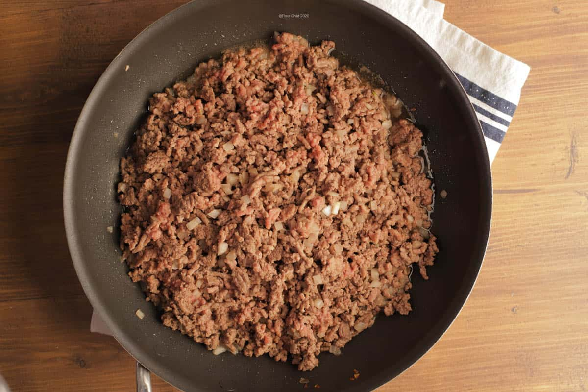 Ground beef browning in a cast iron skillet