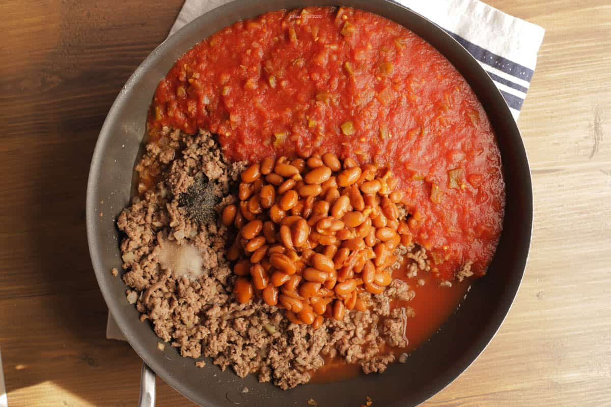ground beef in skillet with picante sauce, chili beans, salt and pepper added