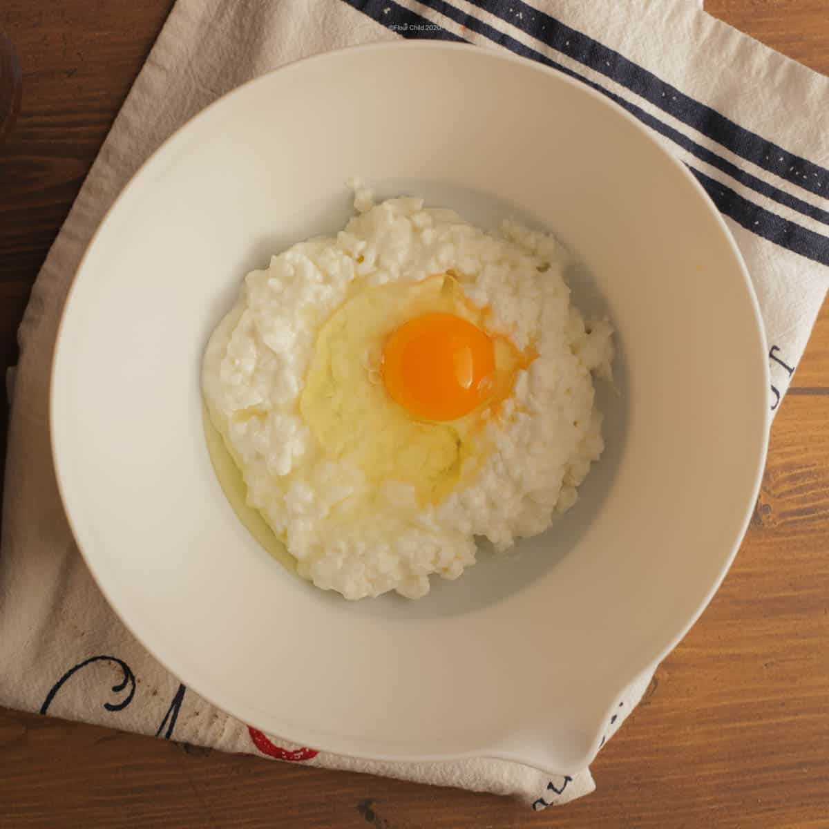 Cottage cheese in mixing bowl with egg added in