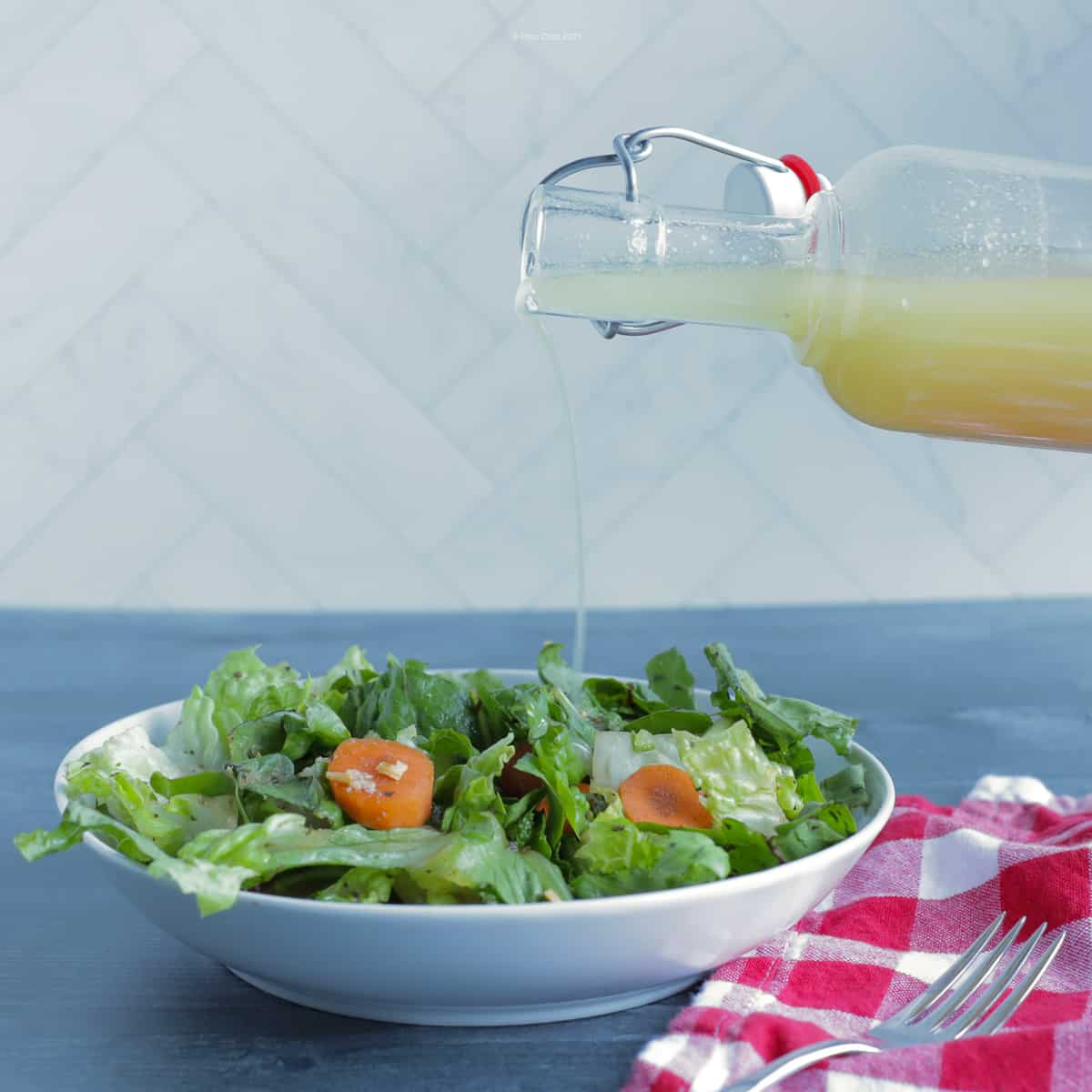 Salad dressing in a glass bottle, being poured over a green salad I a white bowl, with a red checked napkin next to it