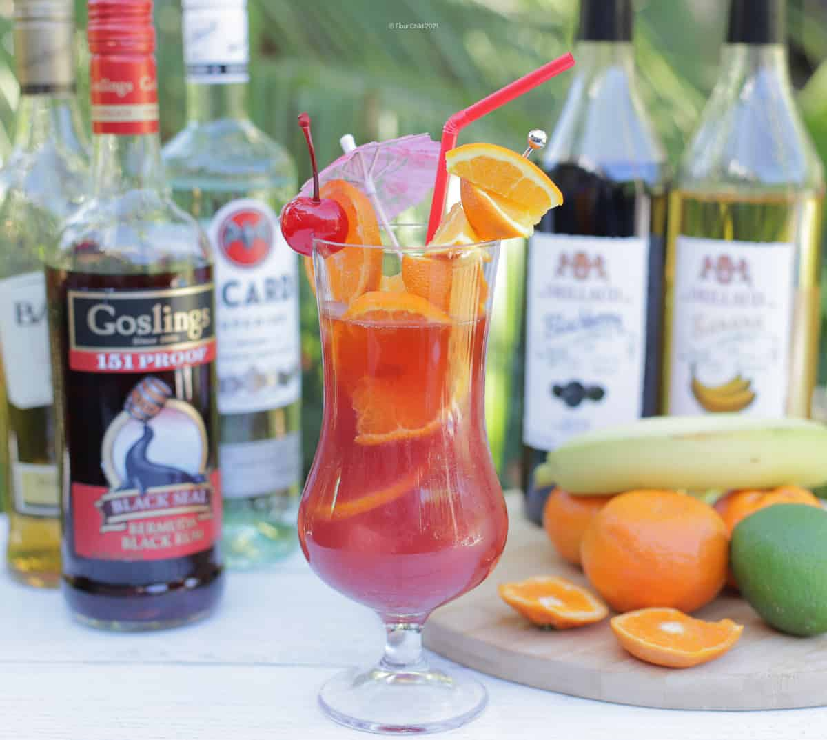 A Rum Runner Cocktail in a hurricane glass with ingredients