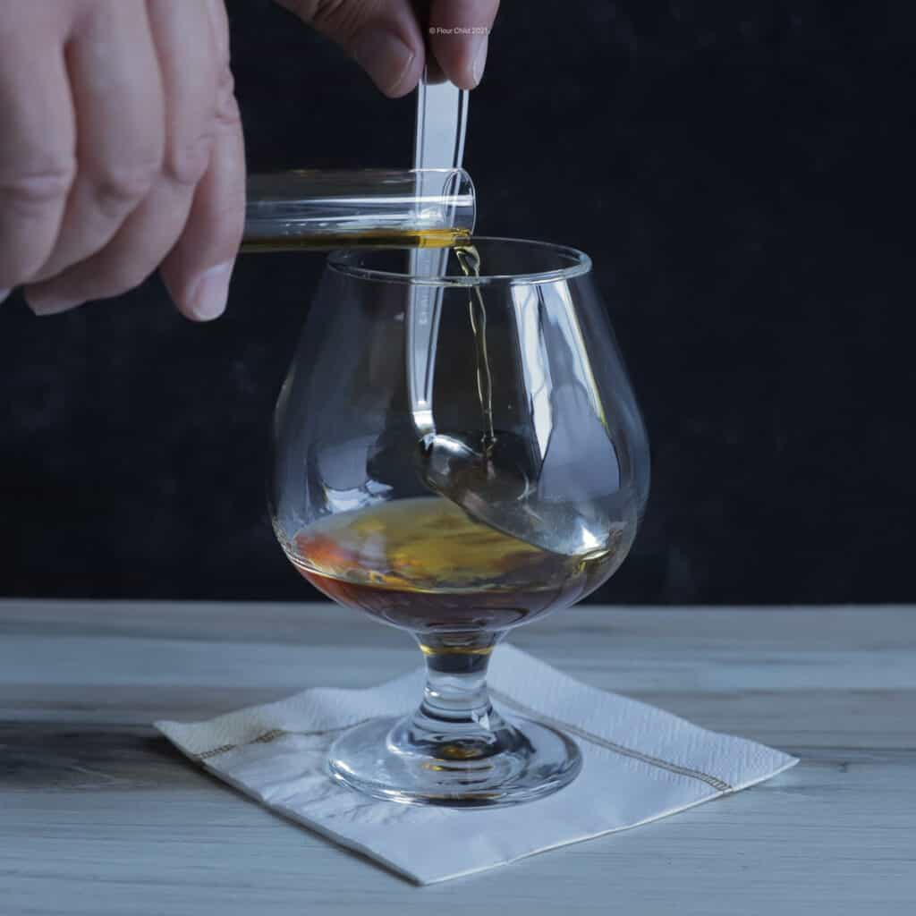 Demonstration of mixing Benedictine and brandy for a B&B cocktail