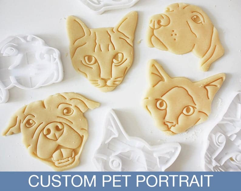 Four cookies of custom cookies of cats and dogs next to their cookie cutters