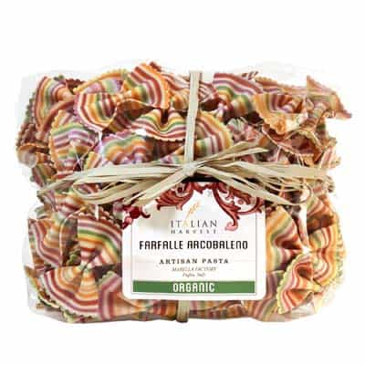 Rainbow farfalle pasta wrapped in a clear cellophane package with a raffia bow tied around the center