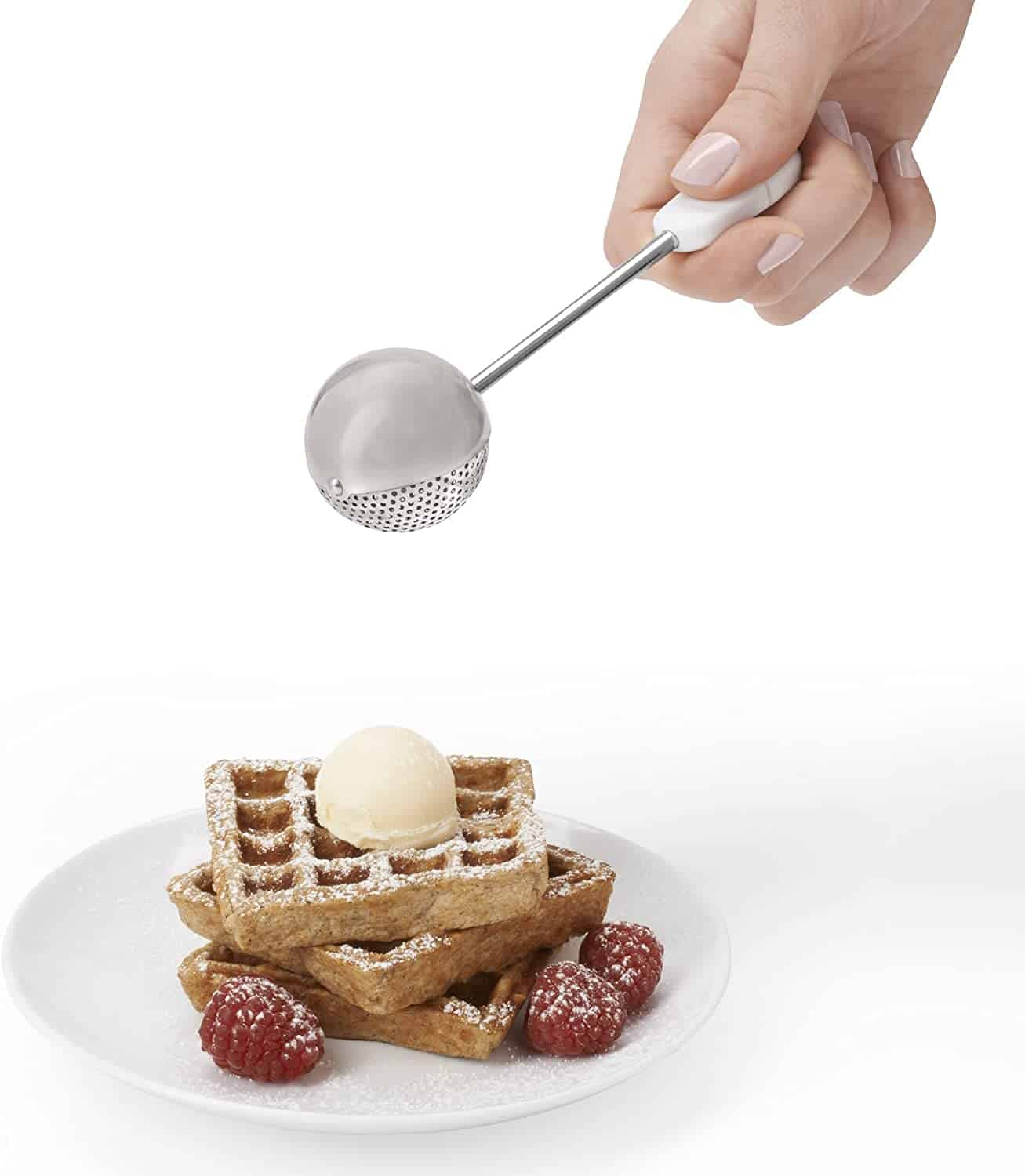 Dusting wand being used to drop powdered sugar over a waffle and berries
