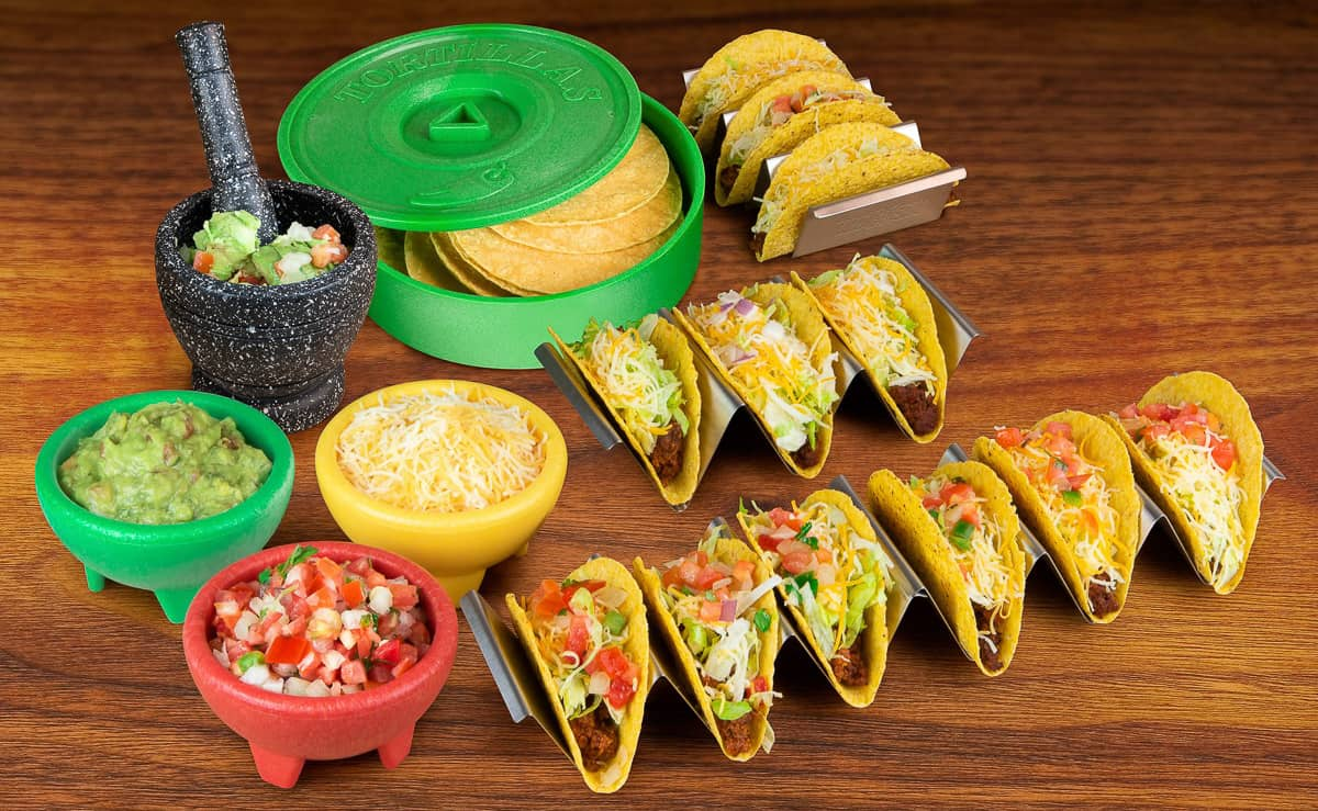 Photo of green tortilla holder with tortillas inside, 3 silver tacp trays each holding tacos, a red, yellow and green bowl filled with taco toppings,