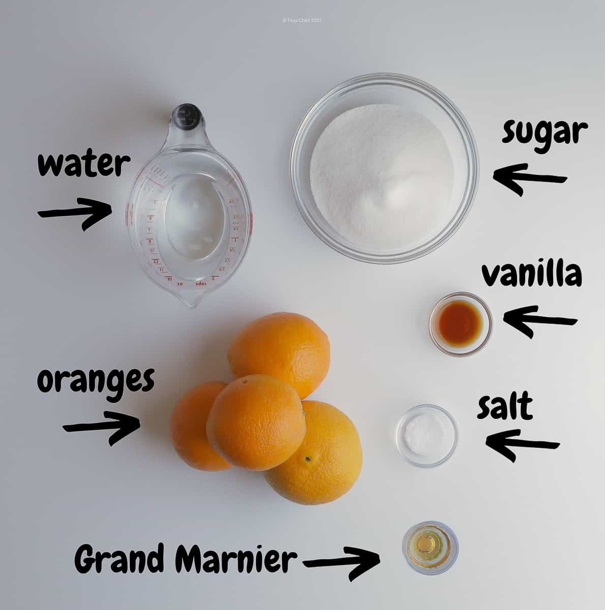Ingredients for candied orange peel set on a countertop, including water, sugar, oranges, vanilla, salt and Grand Marnier