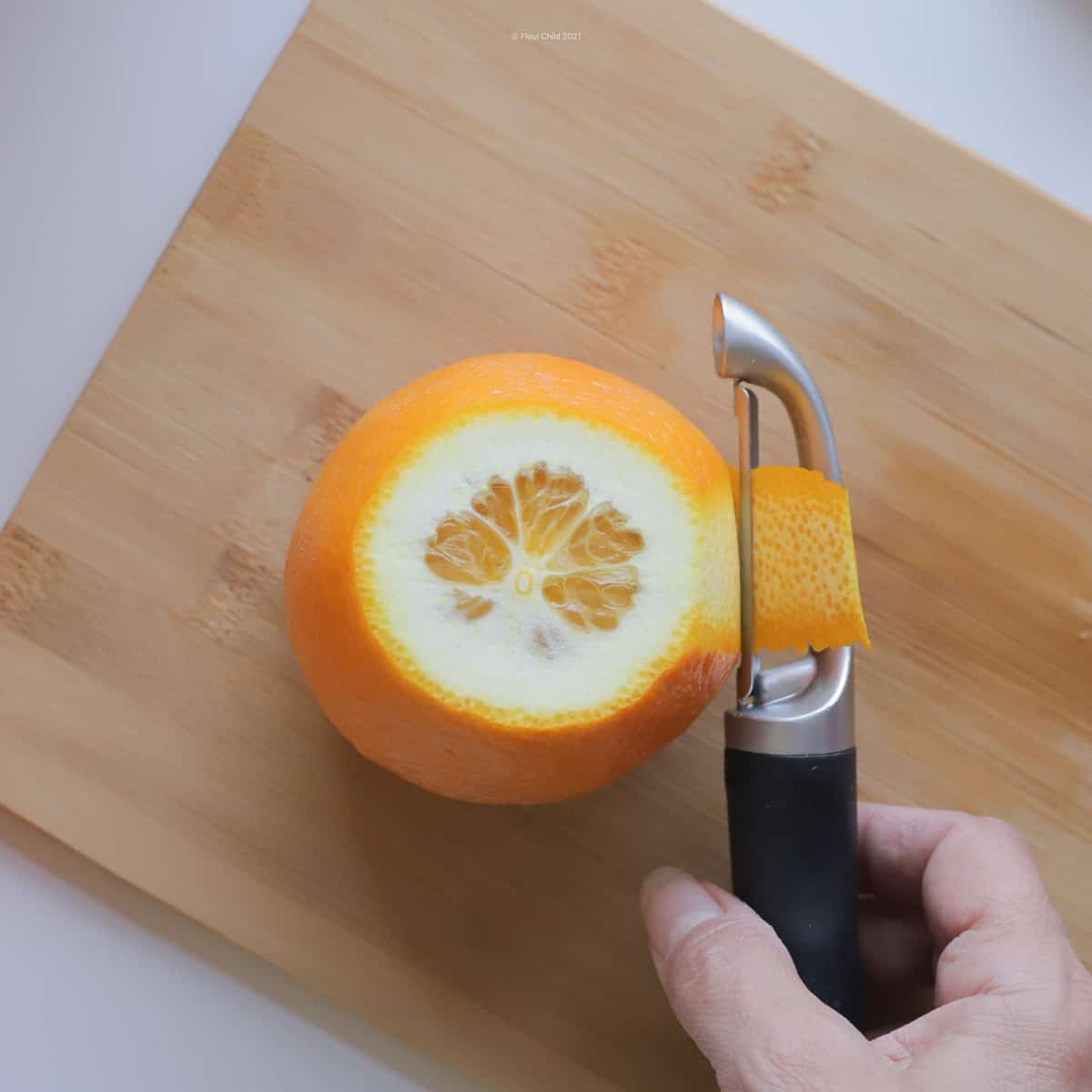 Orange standing on cut-off end; peeler going down the side removing the peel