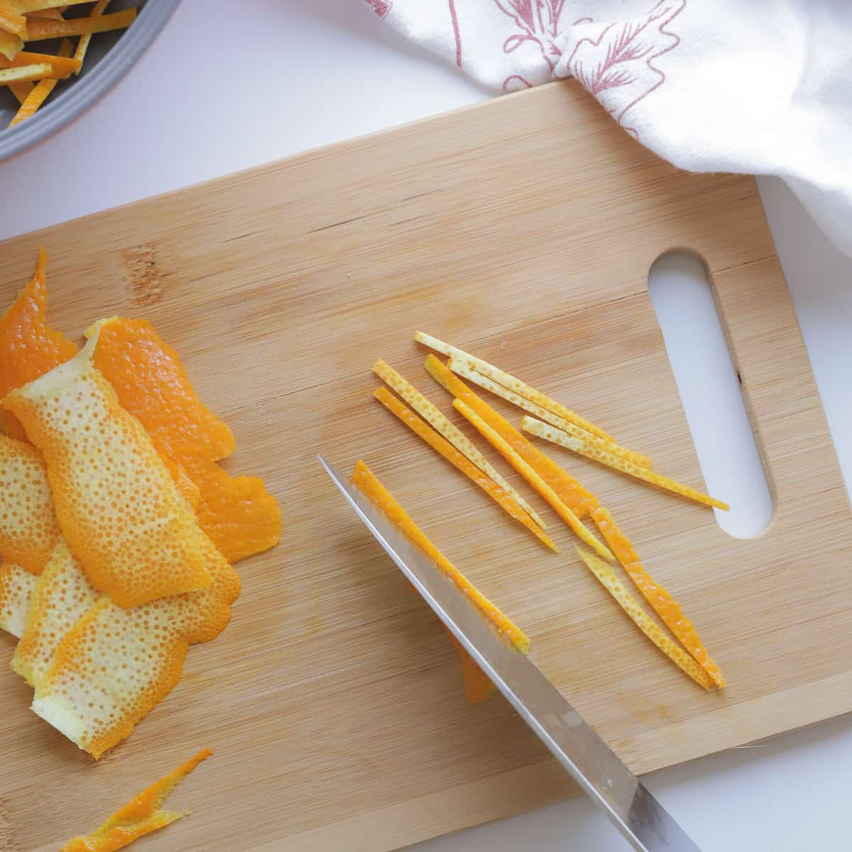 Orange peel being sliced into narrow pieces on a cutting board