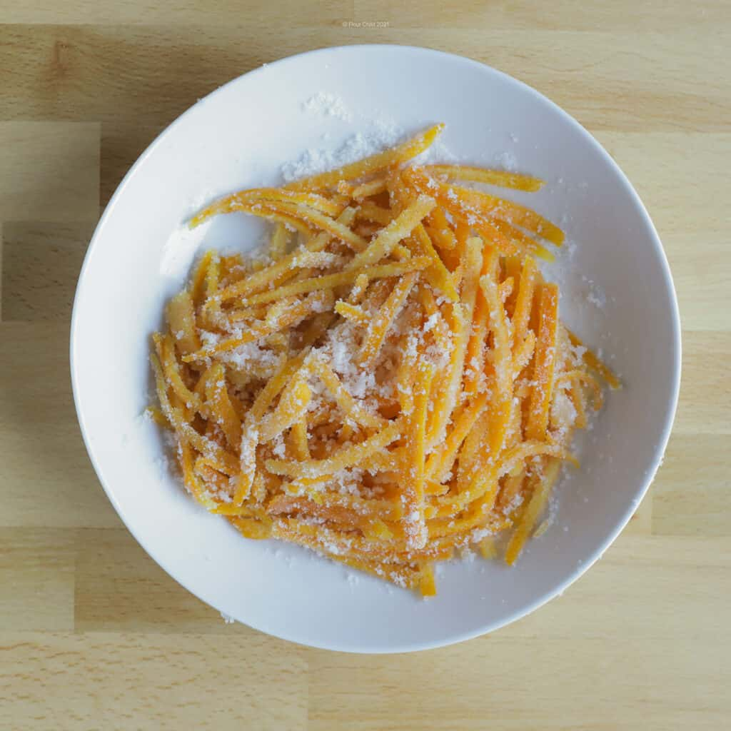 Candied orange peel tossed in sugar in a white bowl