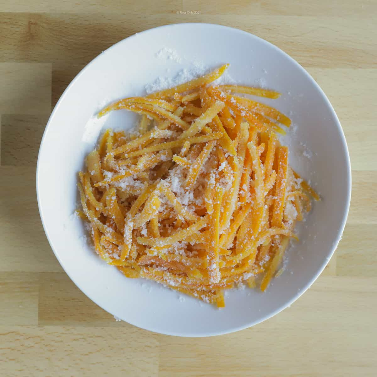 Candied orange peel piled in a white bowl, ready to use as a garnish or eat as a candy