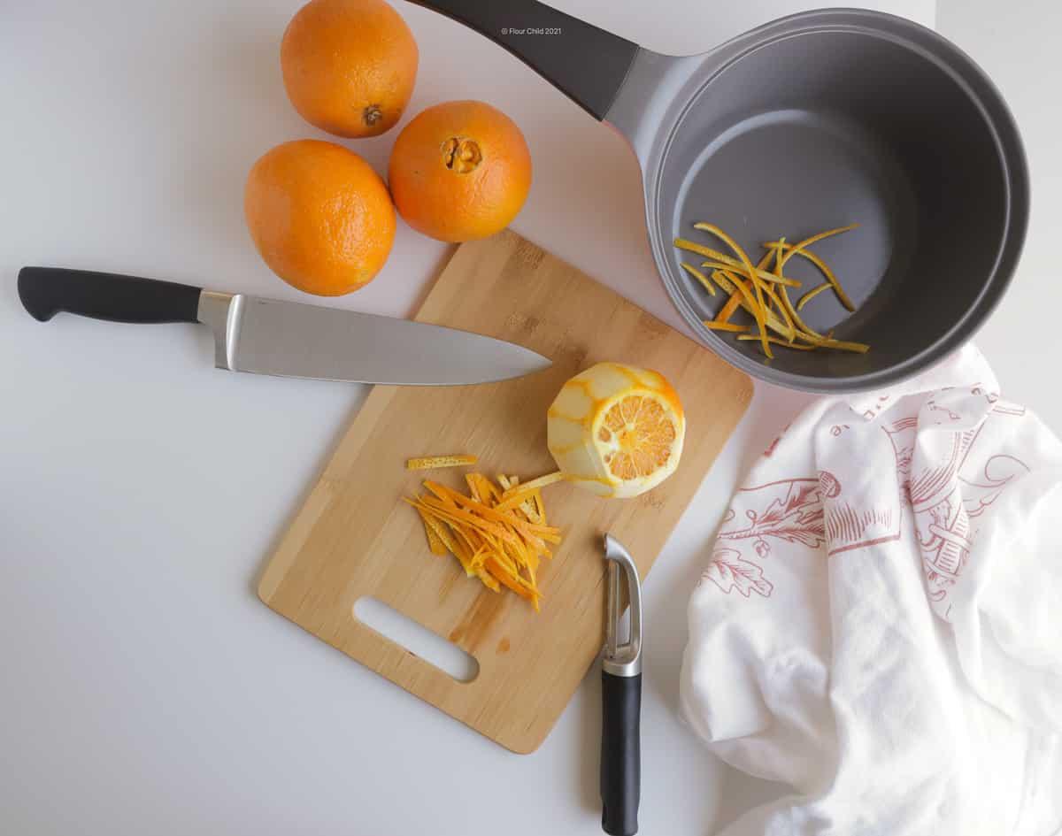 Sliced orange peel on a cutting board next to a peeled orange.