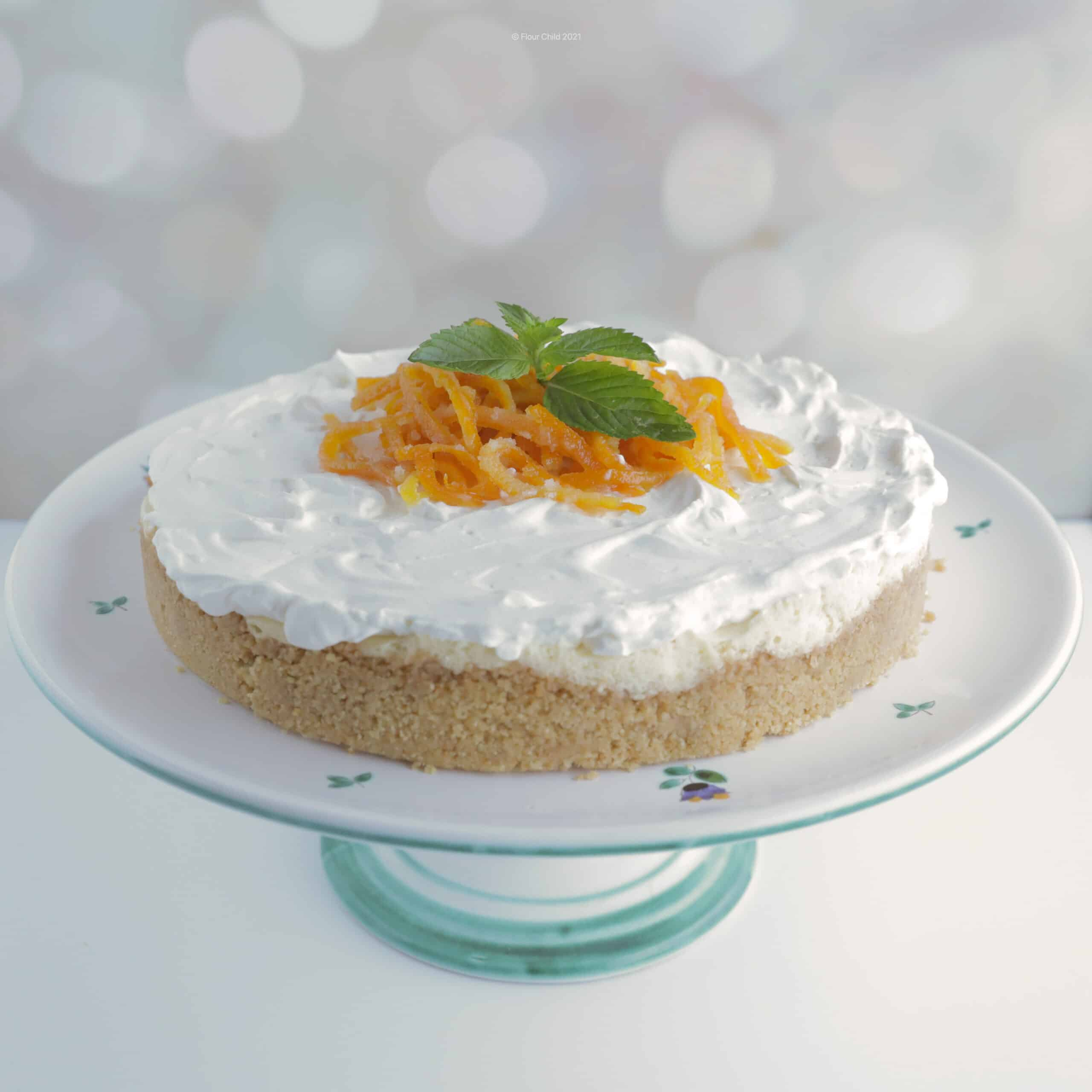 Orange creamsicle cheesecake on a cake pedestal with candied orange peel and mint leaves garnishing the top in the center.